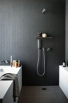 Small matt black rectangle tiles laid in a grid pattern...this bathroom is so cool and those tiles are definitely the feature in this space.