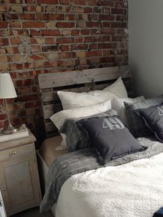Brick wall, pallet headboard, vintage nightstand and gray bedsheets in our bedroom.