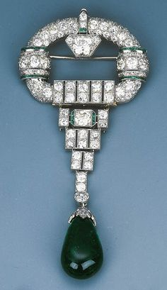 An Elegant Art Deco Diamond and Emerald Pendant Brooch, Circa 1930, with concealed pendant hook, in case, 10.5 cm long.