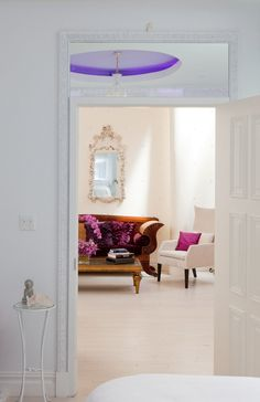 Tracie Martyn Salon Interior Lounge Area....I like the color of the wall with the mirror hanging on it