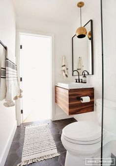 GUEST BATH  Wooden vanity with white sink/counter Tilted mirror (dark frame) Darker tile floor (solid or pattern) shower floor/walls white (several types of tile?) White subway vertical Pendant lights vs. sconces