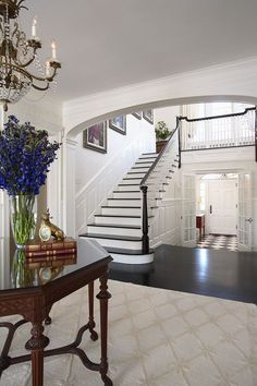 Lovely - view of foyer from living room. Tiled entrance that opens into a 2 story foyer with stairs that do NOT face front door. Architectural Design Studio, Architecture Design, Architecture Interiors, Style At Home, Black Banister, White Staircase, Foyer Staircase, Staircase Ideas, Staircase Design