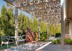 An intricately patterned arbor crafted from aluminum casts lovely patterns of light and shadow across this backyard patio designed by Exterior Worlds Landscaping, including order shrubs for privacy, drought-tolerant plants and a bed of limestone chips for flooring.