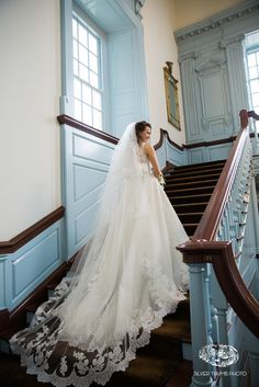 Wedding at Lovett Hall - bride photographed in The Henry Ford Museum clock tower by Silver Thumb Photo. Dress is Pronovias Prima Dona. A-line princess wedding dress in tulle with lace and guipure appliqués. Bodice with v-neck and sheer overlay adorned with appliqués front and back. Cathedral veil 2853 made to match.