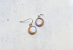 Orange and white design silver colored dangle glass by Anchy, $7.50
