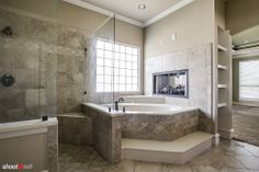 tub next to fireplace, large shower, gray tile
