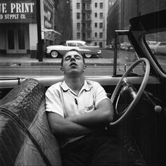 Man in a white shirt asleep with his arms crossed in a convertible.