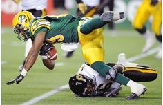 Edmonton Eskimo Marcus Henry is tackled by Hamilton Tiger-Cats Armando Murillo during the first-quarter of their Canadian Football League game at Commonwealth Stadium on Friday, Oct. 5, 2012.