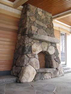 Boulder stone fireplace with antique granite mantel and curved stone hearth