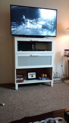 We took an old Ikea dresser and converted it into a TV stand.  We removed the panel from the first drawer and cut a hole in the back panel for the equipment.  We kept the drawer in the middle for storage and removed the bottom drawer to use as shelf.