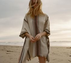 In raw silk stripe, the DOEN Idyllwild Poncho is a great transitional popover or beach cover up. The hand embroidered blanket stitch, and linked blanket stitch, give this piece a soulful 1970's beach