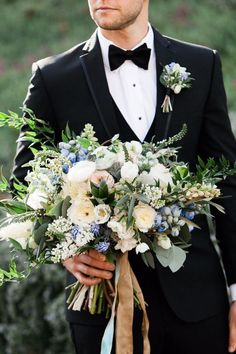 groom holding the bride's bouquet