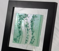 This piece of fused glass wall art is beautiful and full of texture. It has a bit of a beachy, sea glass look to it. It is made of several layers of transparent sea green iridescent glass and crushed glass with bits of dichroic glass that make it sparkle. The colored glass is attached to a piece of clear glass background (The color of the wall will show through the piece) and a wooden black frame with an attached saw tooth hanger. The frame measures 10 X 10 square and is approximately 1…