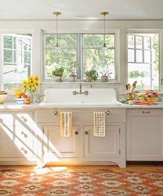 White kitchen with glass pendants in front of windows