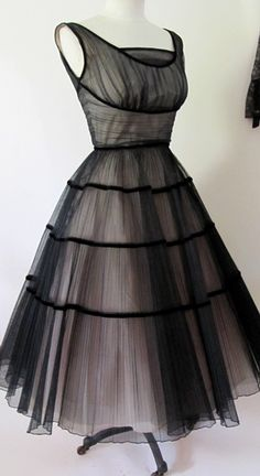 1950's  vintage black and pink tulle dress. Layers and layers of pleated black tulle over a pink satin under skirt. Black velvet trim adds definition to the design. Shelf bust construction, pinched at the waist, full circle skirt, back metal zipper.