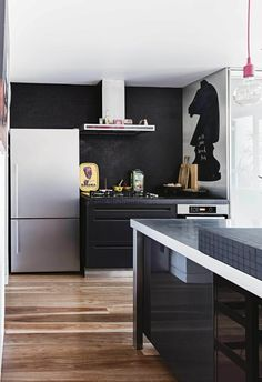 Kitchen in Victorian terrace with timber floorboards and matte black feature wall. Black cabinetry complements stainless steel appliances.