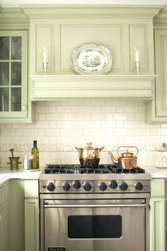 """Mantel-Style Range Hood: """"Subway tile and a mantel-style hood age the range, one of the few modern-looking features in this kitchen. The vintage-style vent hood meshes perfectly with the cabinetry, bringing the kitchen together. The stainless-steel range adds a contemporary twist while retaining the kitchen's elegant style."""""""