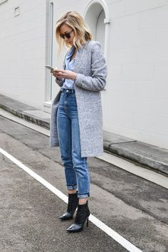Long grey winter coat, lightblue shirt, blue jeans and black shoes.