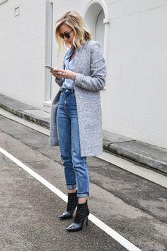 Long grey winter coat, lightblue shirt, blue jeans and black shoes.