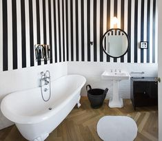 Bathroom Palette: black & white - white bathtub and black wall with golden mirror frame.  [Selection of bathroom images depending on colour shades] ITA: Il bagno in bianco e nero - galleria di immagini Design by BMMC Studio - Milan