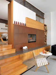 designer Peter Fleming's double-sided fireplace helps heat the living room and principal bedroom. To give the metal surround a warmer look, Peter rusted it with a solution of rock salt and warm water, then waxed it to a dull finish.
