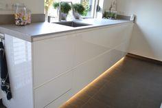 Greeploze hoogglans witte keuken met plintverlichting.