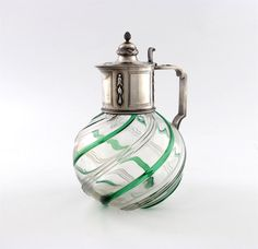 Fabergé silver-mounted glass claret jug, Moscow, 1896-1908. The spherical glass body moulded with plain and green spiral bands, the neck mount with alternating rectangular reserves and chased and engraved husk and bead swags in concave surrounds, the geometric handle with ribbon-tied reeding, the cover and scroll thumb-piece engraved border, the raised domed centre with a band of ribbon-tied laurel beneath and a pine-cone finial, gilt interior.