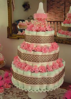 Diaper cake ideas: topper made with plastic fake baby bottle filled with pink or blue candy.