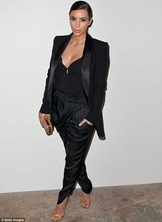 She's all business: Kim Kardashian looked dressed for success in baggy black trousers, blazer with a plunging top at the Marianne Williamson...