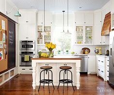 In this quaint kitchen, a beaded-board ceiling, turned legs on the wood-topped island, and classic millwork are all painted white for a look that is cheery and bright. The pantry is hidden behind a message board and the range hood is encased in wood panels to transform this kitchen into a personal place to gather.