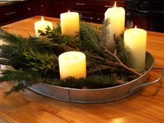 Pine or yew boughs in some sort of rustic platter, with pillar candles. Addition of cloved oranges and maybe a scented herb?