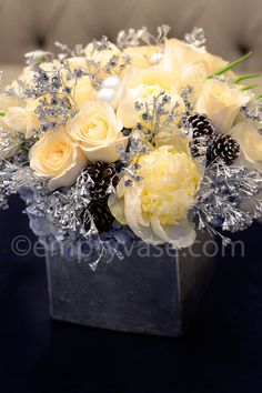 White roses, tulips and peonies, blue hydrangea, silver holiday ornaments, and decorative pinecones in a silver metallic vase.