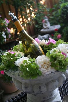 Make a wine cooler by filling a planter with ice and adding flowers around the edge.  Beautiful!