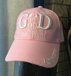 """This pink baseball cap features the message """"God is Good All the Time"""" embroidered in white thread on the front, along with an offset, mirror image to the right in pink thread. Also on the left side of the bill the words 'I Love Jesus' are embroidered in white.  - Six-panel construction. - Embroidered design. - Adjustable velcro-closure at back. - 100% Acrylic."""