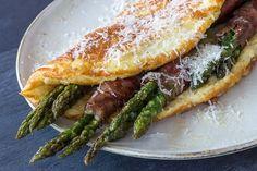 Fluffy parmesanomelet med parmaskinke og asparges | * 1 bundt grønne asparges * 1 pakke parmaskinke eller bacon (ca. 8 skiver) * smør til stegning * 4 æg * 4 spsk piskefløde * 1 håndfuld revet parmesan * salt og peber