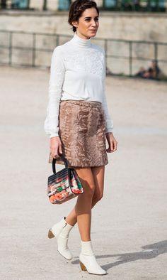 Street style look com blusa branca e saia marrom mais bota branca.