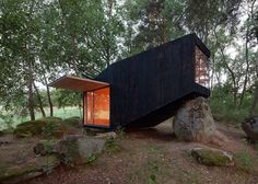 Forest Retreat by Uhlik Architekti rests on a boulder in a Czech wood