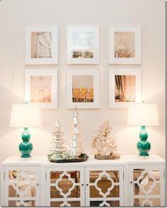 Love this pretty white console with turquoise lamps and that grouping of framed prints are really striking. A simple grouping of mercury glass trees adds a festive touch. .