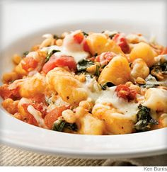 Tasty comfort food with lots leafy greens, tomatoes and beans to add fiber, iron, and antioxidant vitamins A and C!  Try using whole wheat gnocci for additional fiber :)