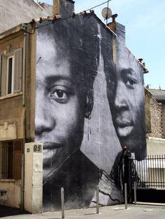 Retour sur le projet UNFRAMED de l'artiste JR à Marseille. Berthe et Diallo sont les grands parents d'Aramata, une jeune et récente habitante du quartier Belle de Mai (3ème arrondissement de Marseille). Cette photo de la famille Traoré (prise au…