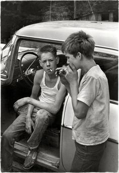 "Cigarette Lighter : 1964    Leatherwood, Kentucky, circa 1964. ""Cornett boys smoking by car."" No after-school soccer for these lads.    Print from a 35mm negative by William Gedney. Gedney Photographs and Writings Collection, Duke University.     (via)"