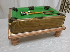 Pool Table Grooms cake  - This was my first attempt at a pool table cake... My husband made the stand.   Edited: Several people have asked how I get the shiney look.  It's a trick I learned at a cake club meeting.  After your fondant hardens,  brush a thin coat of vegetable oil over it.  The fondant will absorb the the oil,  and it does not affect the flavor.  Thanks for the compliments! I love doing wood grain stuff!