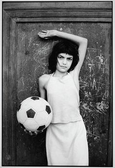 Letizia Battaglia photographed a young girl with soccer ball in the neighborhood where drugs are sold, 1982.