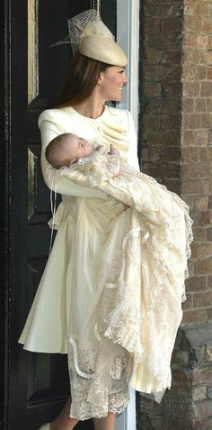 Duchess Kate carries her son Prince George after his christening at St. James's Palace in London on Oct. 23, 2013. She wore an Alexander McQueen dress and Jane Taylor fascinator.