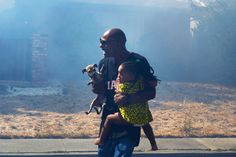 FLEEING: LaRue Montgomery carried his 2-year-old niece, Brianna, and his dog out of his house as a grass fire threatened homes in Fairfield, Calif., Tuesday. About 50 people fled after the roadside fire spread, destroying five homes and damaging 10 others. (Aaron Rosenblatt/Daily Republic/Associated Press)
