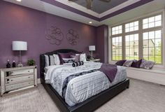 A master bedroom boasting an elegant bed setup surrounded by gorgeous purple walls and a stunning purple tray ceiling. Purple Master Bedroom, Purple Bedroom Design, Purple Bedrooms, Bedroom Paint Colors, Master Bedroom Design, Home Bedroom, Romantic Bedroom Colors, Romantic Master Bedroom, Beautiful Bedrooms