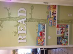 Ikea picture ledge shelving used for a child's reading nook, complimented by a hand painted wall mural.