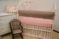 A leopard print padded crib rail guard keeps the teething toddler safe from metal cribs