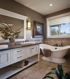 Winlock Parade Home Master Bath - Spa-like master bathroom with pedistal tub and furniture piece vanity. By New Tradition Homes