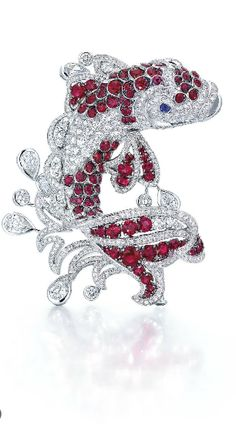 A RUBY AND DIAMOND BROOCH, BY GRAFF Designed as a circular-cut diamond koi with circular-cut ruby accents on the body, fins and tail, swimming within openwork water motifs lined with circular-cut diamonds and collet-set pear and circular-cut diamond droplets, mounted in gold, 6.7 cm Signed Graff, no. GP10792